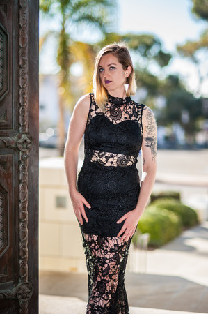 Elegant evening wear on alternative blonde model in black lace against backlit gateway to city.  Shot in downtown Ventura on February 4th, 2018 in California, United States.