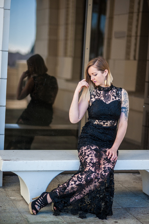 Alternative blonde model looking over shoulder while wearing black lace formal gown reflected in plate glass window.  Shot at Ventura City Hall on February 4, 2018 in California, United States.
