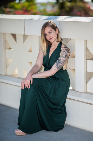 Pretty blonde modeling green halter top gown seated along on lower step of decorative walkway railing at Ventura City Hall on sunny day in February, 2018 in California, United States. Stock Photo