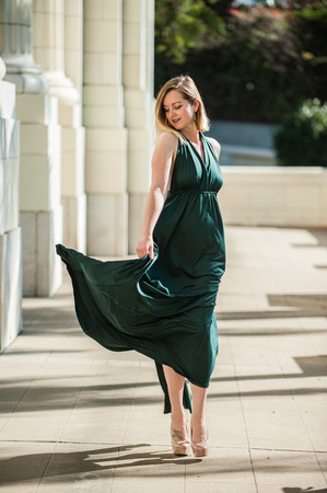 Beautiful blond walking with confidence and glee as her emerald green halter top dress dancing with each step.