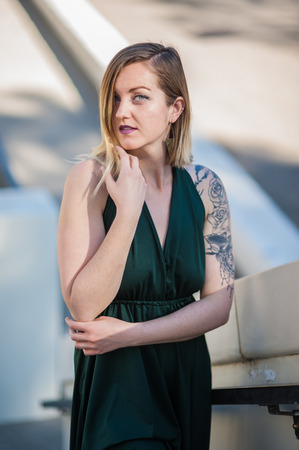 Portrait of modern blonde model with tattoos and pretty face on stairs. Imagens