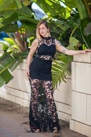 Tattoo model in formal black lace gown posed against white brick wall and foliage. Imagens
