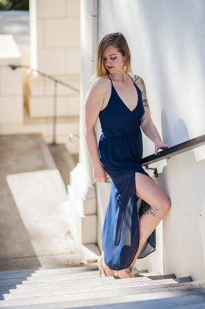 Blonde in blue sheer dress showing bare thigh as she looks back down the stairs. Sunny winter day at Ventura City Hall building in California, United States.