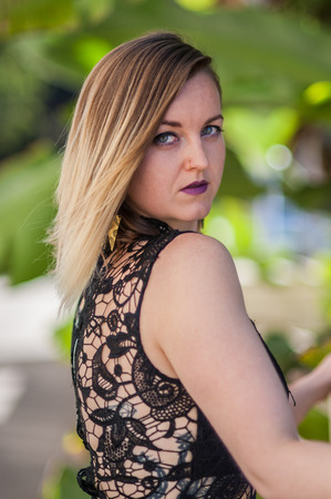 Beautiful young woman looking over shoulder in sleeveless black lace dress.