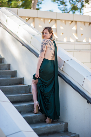 Bare leg showing through emerald green formal gown worn by blonde model stepping up stairs to Ventura City Hall on February 4, 2018 in California, United States.