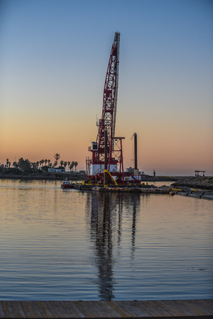 Colorful reflection of dawn light and dredging crane in morning ocean water surface. Stock Photo