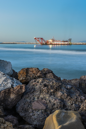 Dredge boat guided by the morning lights working in the harbor with boulders in the foreground. Stock Photo