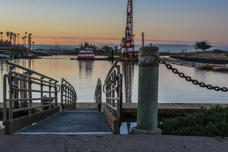 Dawn light reflected in marina water at end of gangway ramp.
