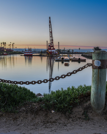 Maine chain links reveal reflection of marine crane in Ventura Marina ocean water at dawn. Stock Photo