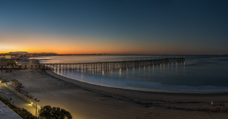 Dawn breaking the dark sky over Ventura Pier with lamps reflecting off ocean surface.