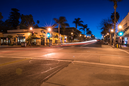 Gradient shades of blue and purple in the morning sky as headlights streak by Starbucks on Main Street in Ventura, California on February 24, 2018 in United States.