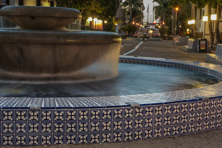 Pair of fountains connected by small canal along Figueroa Street in city of Ventura in early hours of dawn.