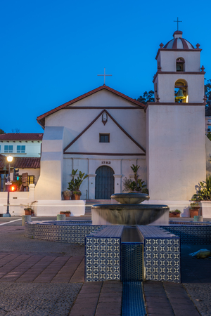 San Buenaventura Mission on Main Street in City of Ventura under blue sky behind water fountain and canal looking up Figeuroa Street toward bell tower.  Shot on February 24, 2018 in California, United States.
