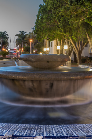 Street lamps shining over water fountain as dawn light begins to illuminate the sky. Stock Photo