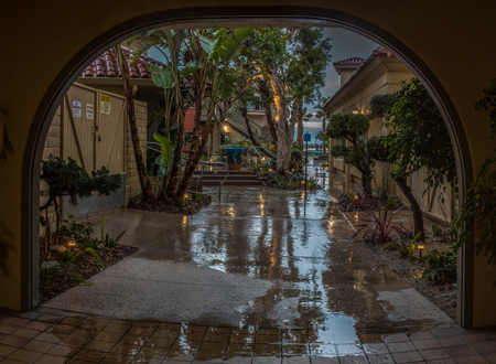Arch in Ventura Harbor Village shows reflected trees on sidewalk due to early morning rain storm on March 3, 2018 in California, United States.