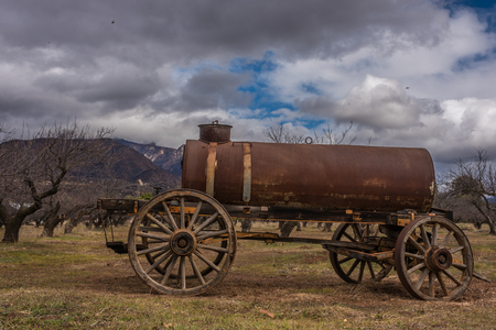 Vintage water tank trailer sitting under winter cloudy sky in the orchard.