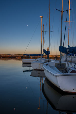 Small sail boats floating in calm marina cove as dawn breaks under full moon.