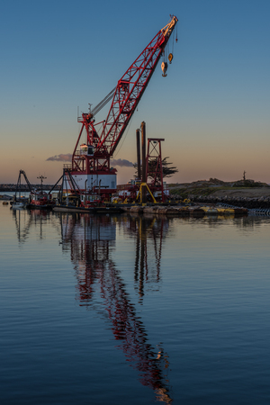 Marine floating crane reflected in calm water of the cove in the early hours of dawn. Stock Photo