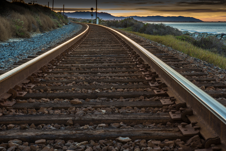 Train tracks heading toward the sunrise curve out of view along the ocean. Stock Photo