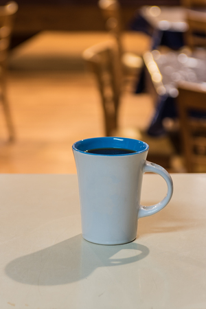 Cup of freshly brewed coffee on waiting on counter top at breakfast cafe. Stock Photo