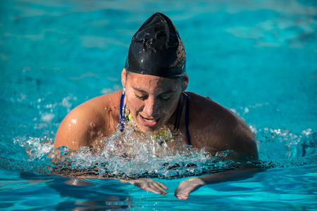 Female swimmer athlete showing discomfort in face competing in race without goggles on.