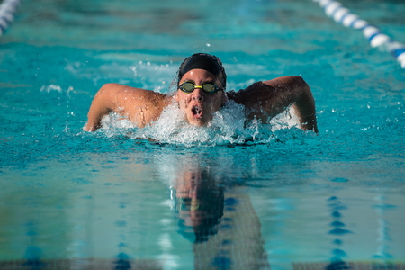 Face and googles of female sprint swimmer reflected in pool water as she breathes mid stroke during race.