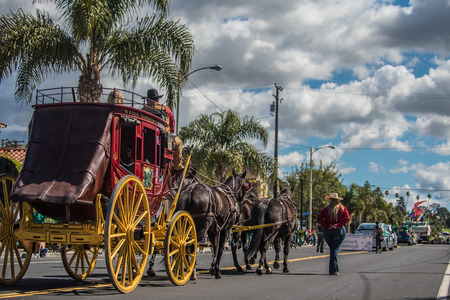 Classic Wells Fargo stage coach drawn by four horse team heading up Main Street in Ventura on Saint Patrickss Day Parade on March 17, 2018 in California, United States.
