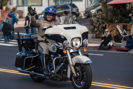 California Highway Patrol officer on motorcycle waves to crowd during annual Saint Patricks Day Parade in Ventura, California on March 17, 2018 in United States.