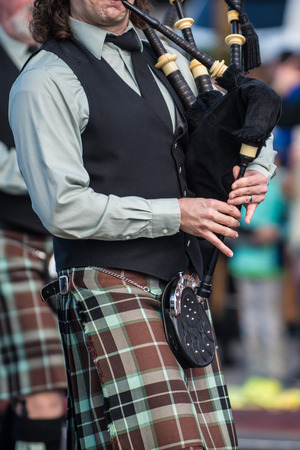 Bagpipe player mouthpiece and hands making music in traditional Irish kilt.
