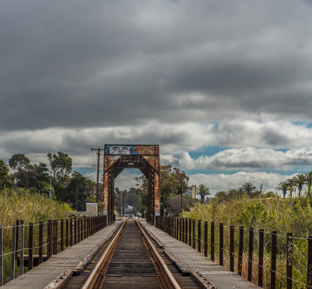 Graffiti covered and rusty steel train trestle spans through the Hobo Jungle of Ventura toward stormy clouds in the sky.