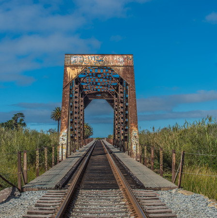 Blue sky is the backdrop for the iron train bridge passing through the reeds of river crossing. Editorial
