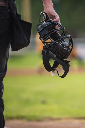 Baseball umpire holding mask in hand as he looks on the field to make a call.