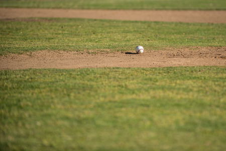 Baseball casting long shadow on the dirt of the field pitching mound. Stock Photo