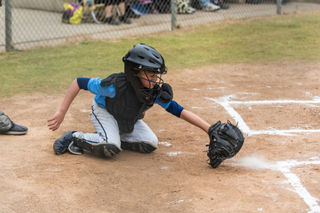 Skilled little league baseball catcher scooping a low pitch out of the dirt as it kicks up a cloud of chalk dust. Stock Photo