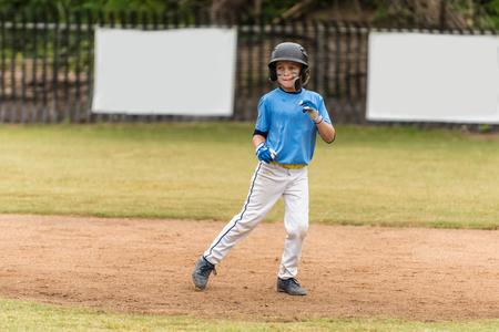 Little league baseball all star in blue uniform leading off on the infield dirt as a baserunner.