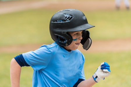 Close up of little league baseball players face showing eye black and concentration heading to first base. Stock Photo