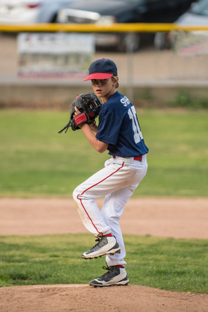 Baseball pitcher keeps eyes on the target as he winds up to pitch.