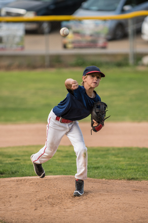 Youth baseball pitcher releases ball with look of expecting a strike out. Stock Photo