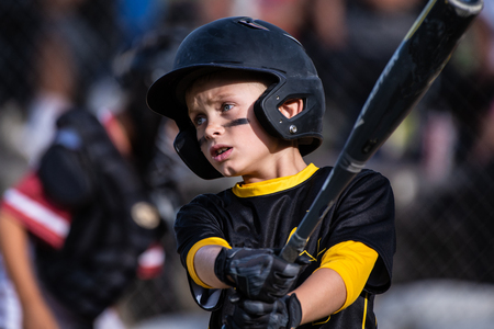 Youth baseball player swinging his bat with intense expression on his face.