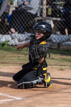 Skilled youth baseball catcher secures the pitched ball in his glove.