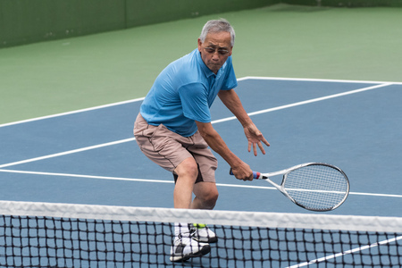 Healthy Chinese elderly man showing flexibility while reach for the low tennis backhand volley.