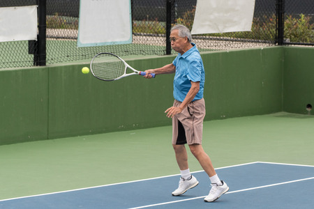 Skilled elderly Chinese tennis player connecting on a forehand ground stroke in a match. Stock Photo