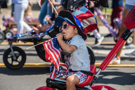 Young child wearing patroitic red, white, and blue colors of the flag while participating in Independance Day pushem pullem parade in Ventura, California on July 4th, 2018. Editorial