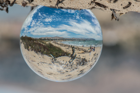 Hanging fish eye globe showing distorted view of beautiful beach day on a typical sunny summer day in California.