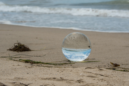 Glass sphere lying on sandy beach inverting the ocean and sky behind it.