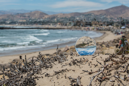 Sunny summer day on the Ventura beaches with puffy clouds visible in blue sky through round sphere lens on sand.