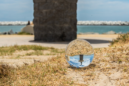 Ventura Harbor mouth in southern California has the Sotor mermaid statue standing as viewed here through crystal globe lying on the adjacent sand.  Photo taken on July 5th, 2018. Stock Photo