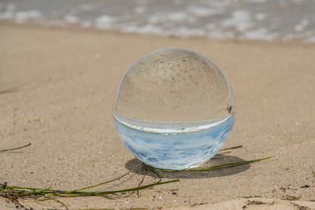 Glass globe on beach shore looks to be full of sky and magnified sand. Stock Photo
