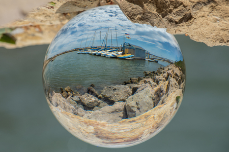 Fish eye view of Ventura sailing center in marina waters bordered by rock jetty.