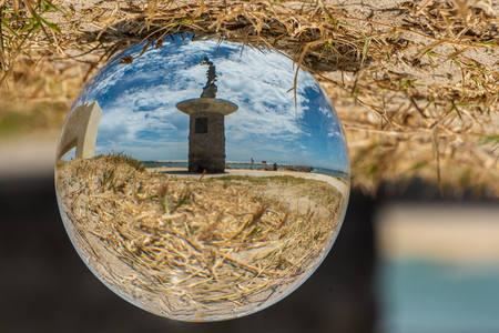 Andrea Sotor mermaid statue standing at Ventura Harbor entrance as seen through fish eye globe with cloudy blue sky on July 5, 2018 in California.